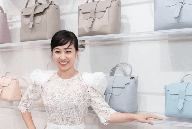 Coral Chung in front of her bags