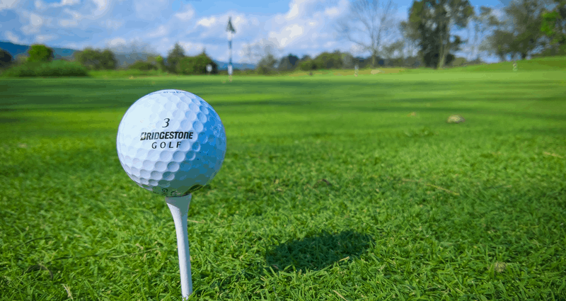 Golf ball on a tee with the hole flag in the background. Green grass and blue sky as the background.
