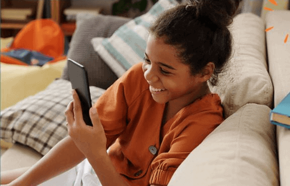 Young girl smiling reading mobile device